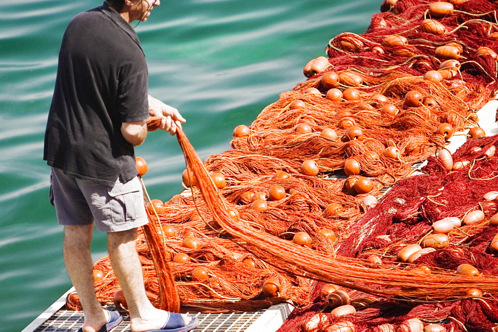 Rear view of a fisherman holding a commercial fishing net, Marina Grande, Capri, Sorrento, Sorrentine Peninsula, Naples Province, Campania, Italy