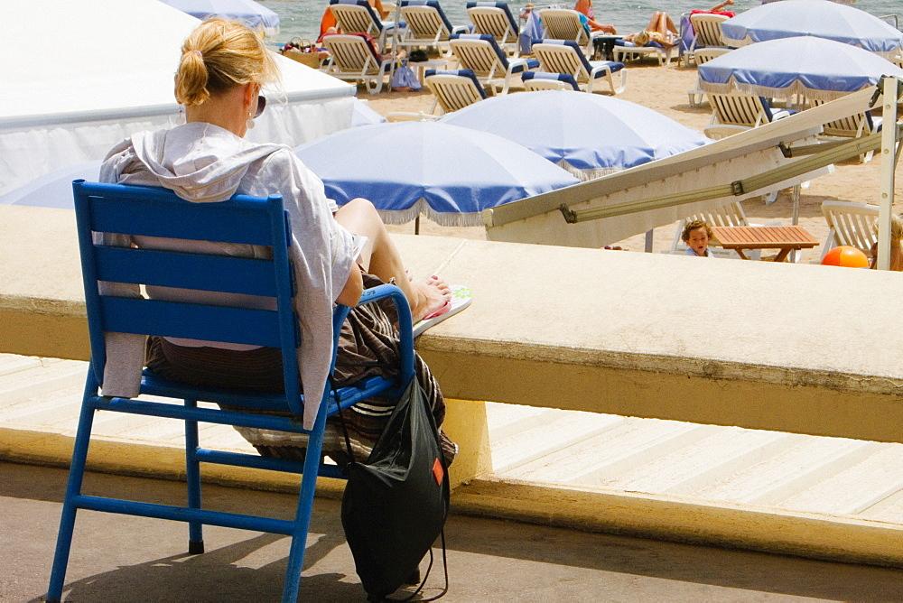 Rear view of a woman sitting in an armchair on the beach, Plage De La Croisette, Cote d'Azur, Cannes, Provence-Alpes-Cote D'Azur, France