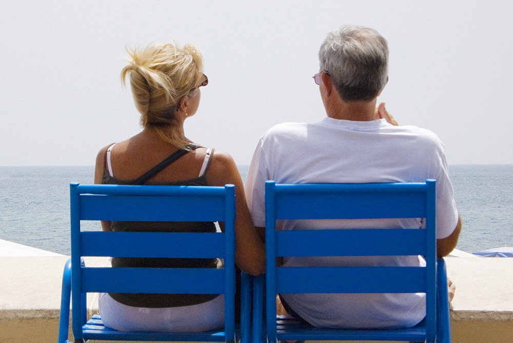 Rear view of a couple sitting in armchairs on the beach, Baie De Cannes, Cote d'Azur, Cannes, Provence-Alpes-Cote D'Azur, France - 788-15721