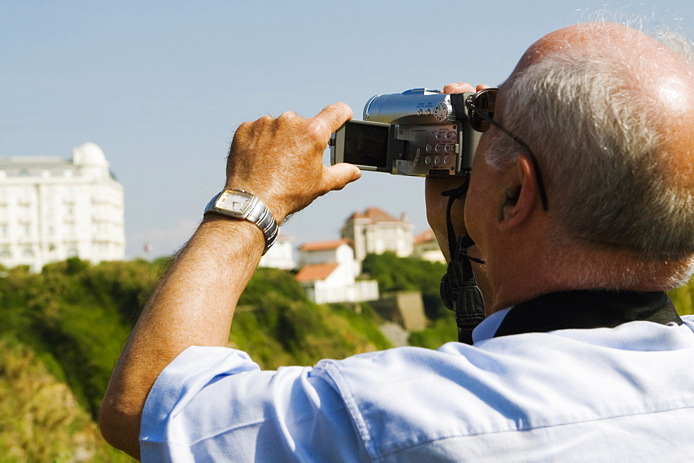 Rear view of a man filming with his home video camera, Biarritz, Basque Country, Pyrenees-Atlantiques, Aquitaine, France
