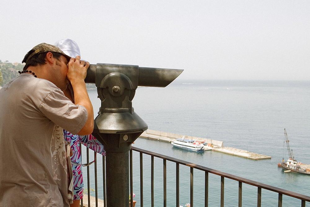 Side profile of a man looking through a coin-operated binocular, Bay of Naples, Via Aniello Califano, Sorrento, Sorrentine Peninsula, Naples Province, Campania, Italy