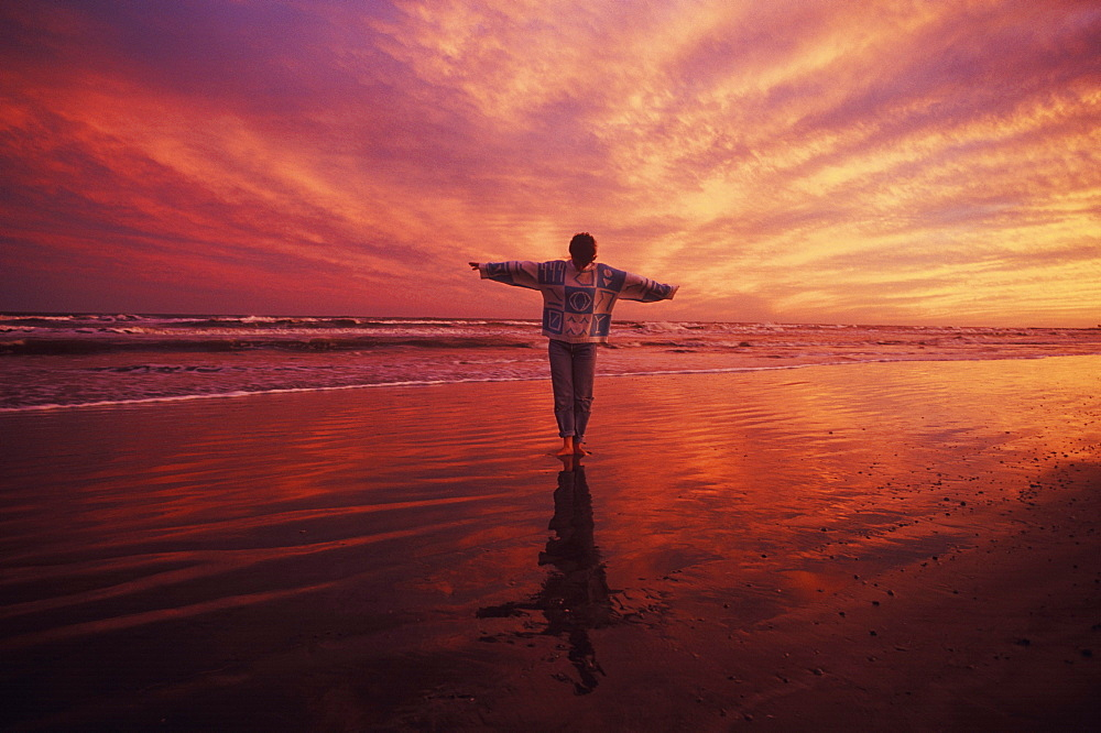 Man standing on the beach with his arms outstretched, Texas, USA - 788-2041