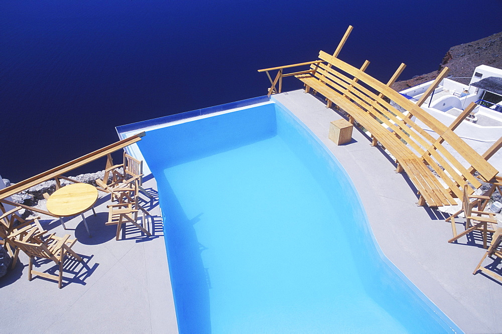 High angle view of a bench and chairs at the poolside