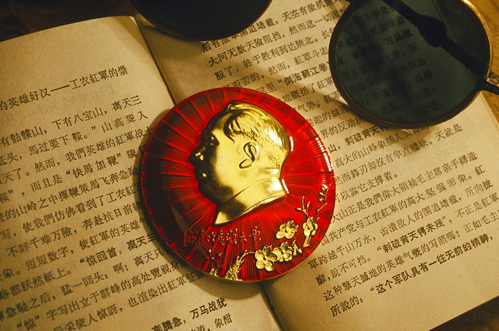 Close-up of Mao Tse-Tung badge on a book