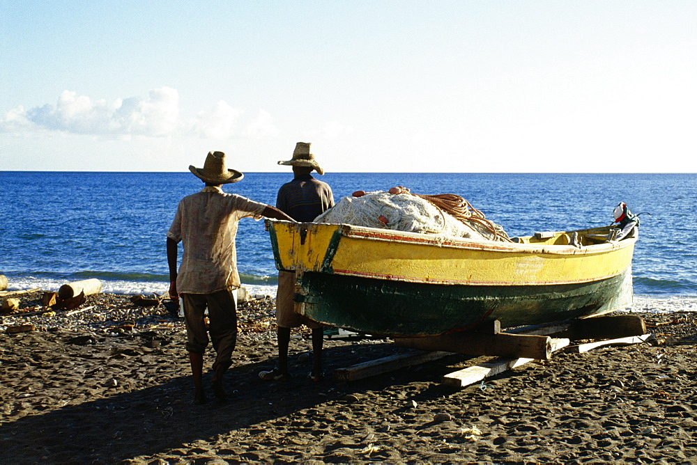 Rear view of two men near a boat on a beach on the island of Martinique, Caribbean