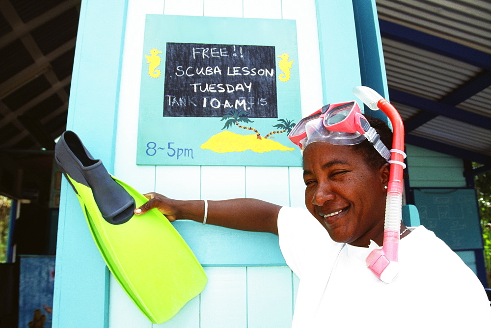 A lady poses in front of a notice while holding a flipper, Port Elizabeth