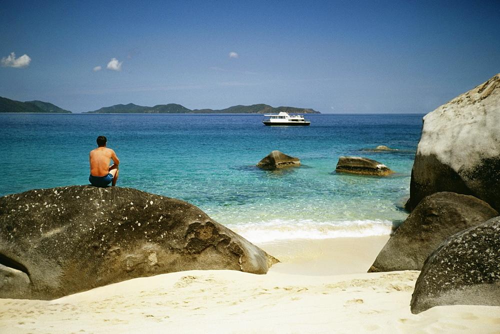 Rear view of a topless man resting on a rock at a seashore, Virgin Gorda, Virgin Islands