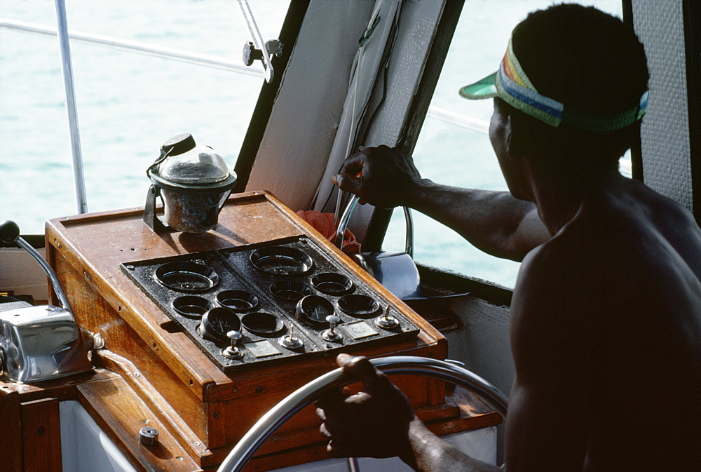 A boat captain navigates a powerboat off the shore of Jamaica