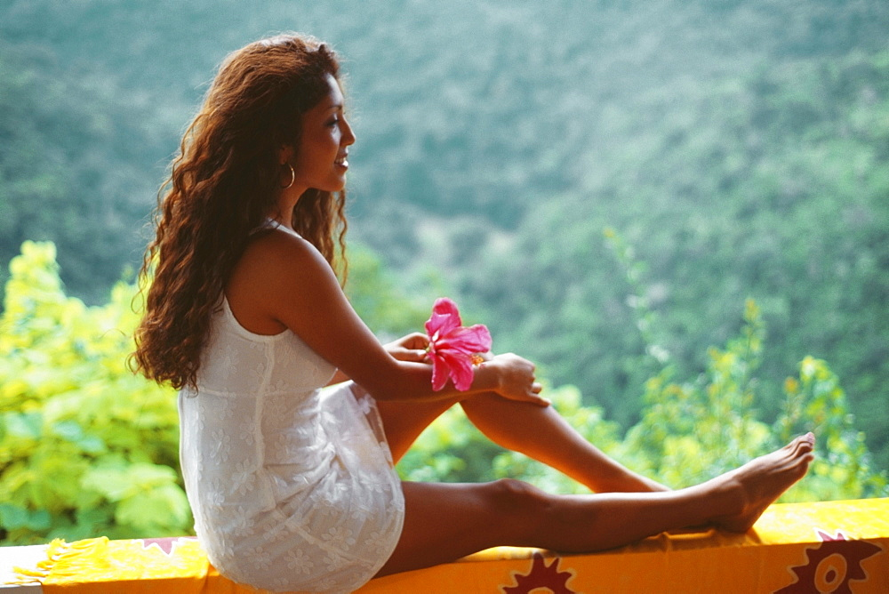 A young woman in white dress is sitting on a ledge, Destiny Villa, Jamaica