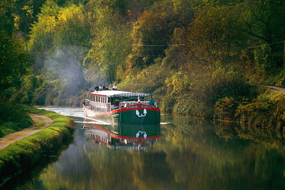 Side view of a luxury barge moving upstream, France