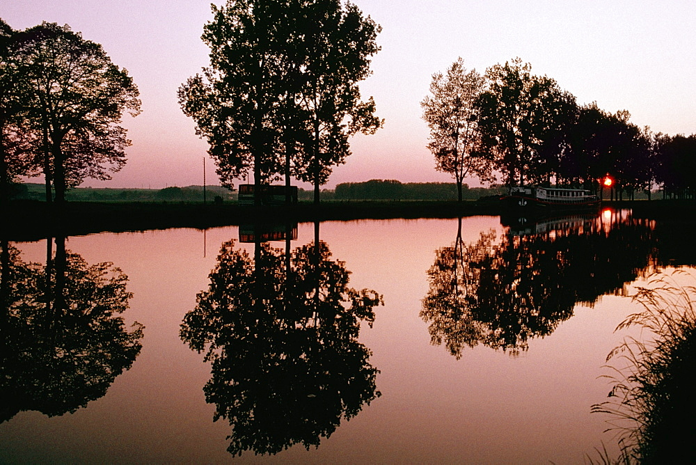 Silhouetted trees being reflected in the Bungundy Canal, France