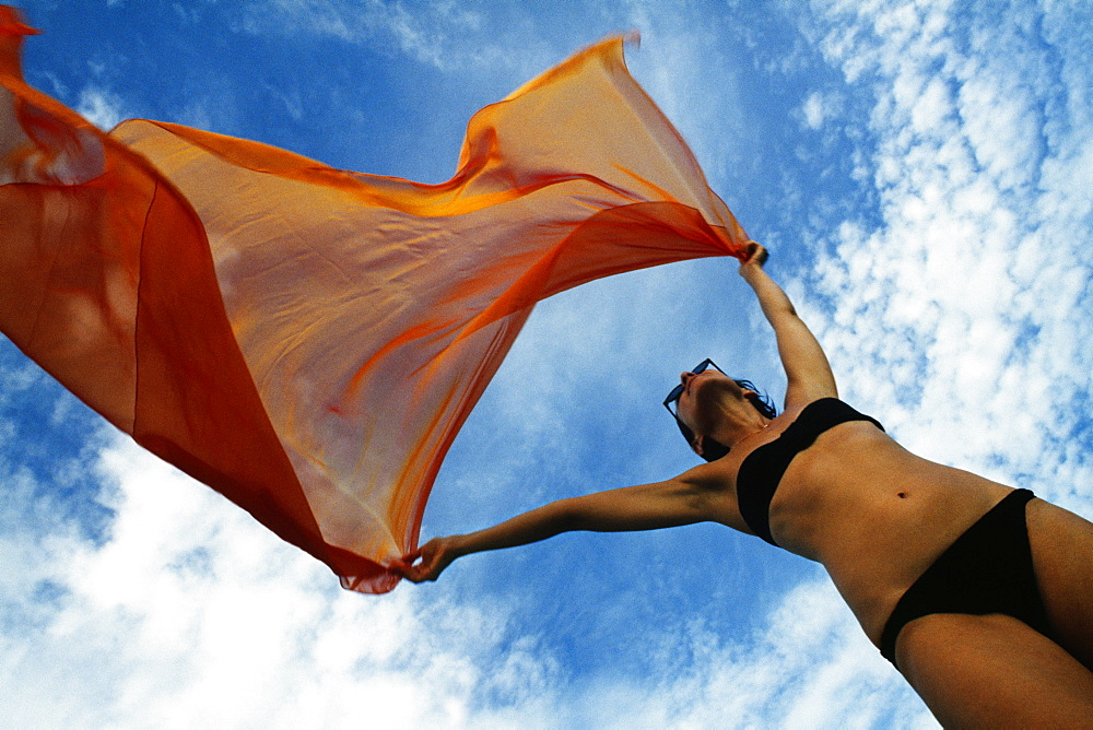 Woman holding a orange colored fabric in the tropical breeze on the island of Barbados, Caribbean - 788-3864