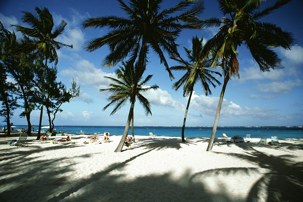 Tourists are seen relaxing on an exotic beach, Barbados