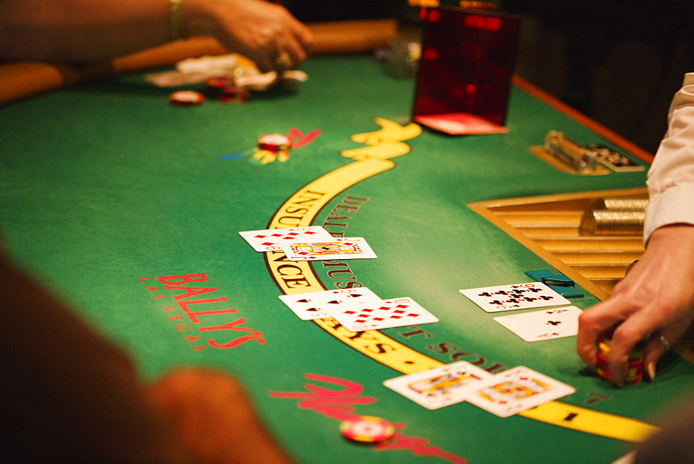 High angle view of a casino dealer picking up gambling chips from a gaming table, Las Vegas, Nevada, USA