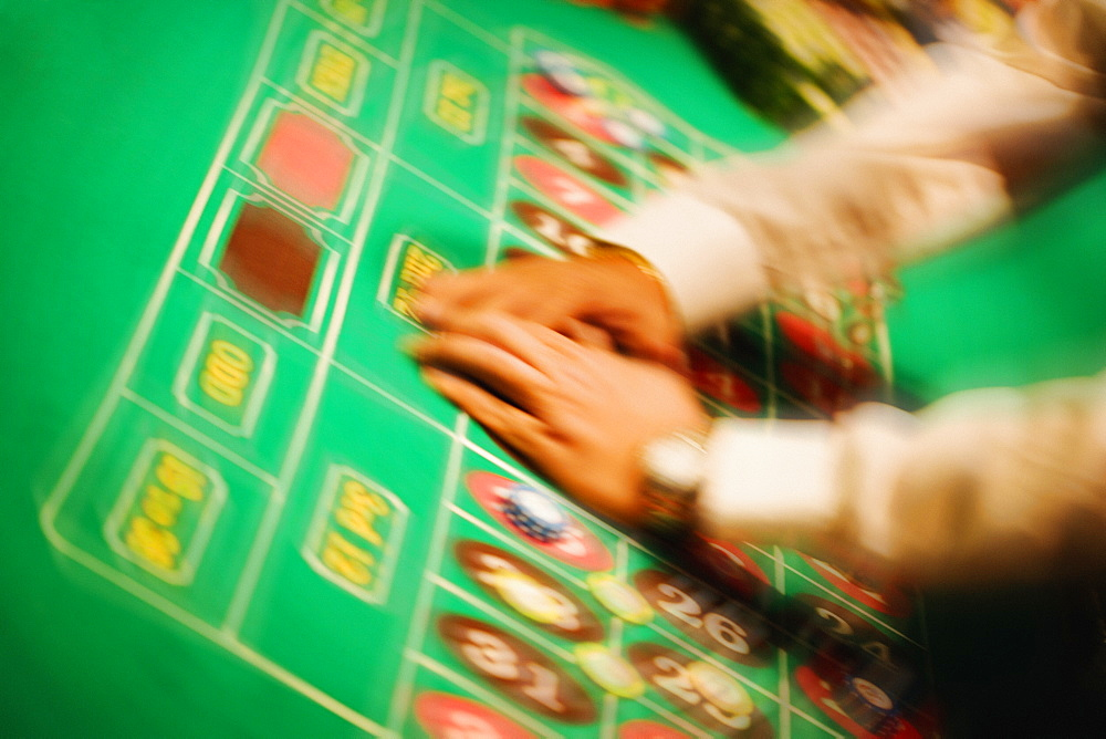 High angle view of a man's hand collecting gambling chip on a roulette table, Las Vegas, Nevada, USA