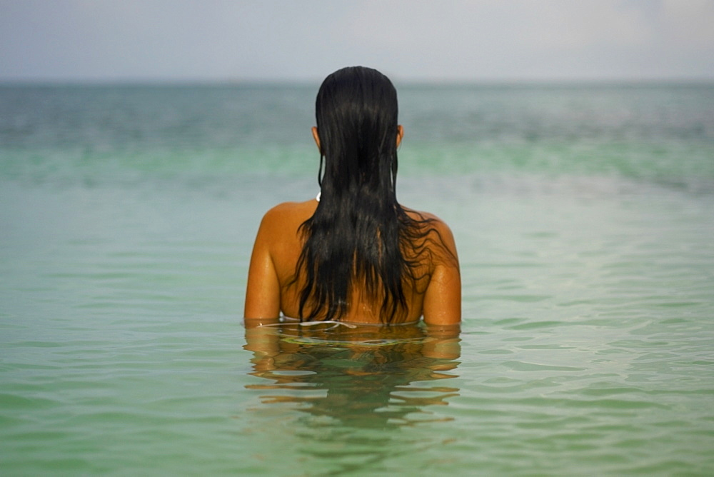 Rear view of a young woman in the water
