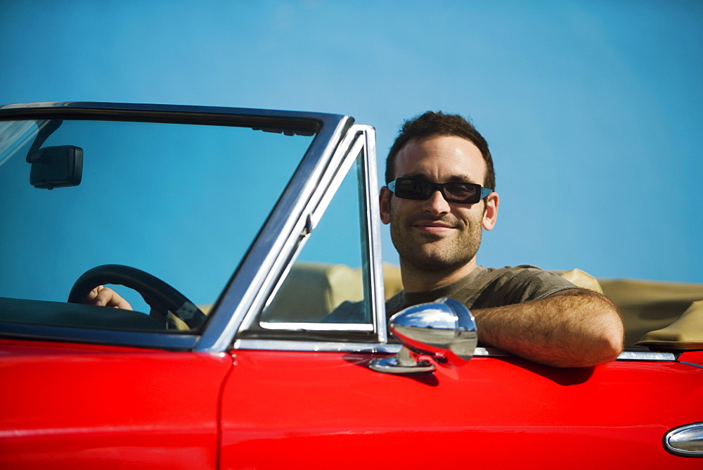 Close-up of a mid adult man sitting in a convertible car, Miami, Florida, USA