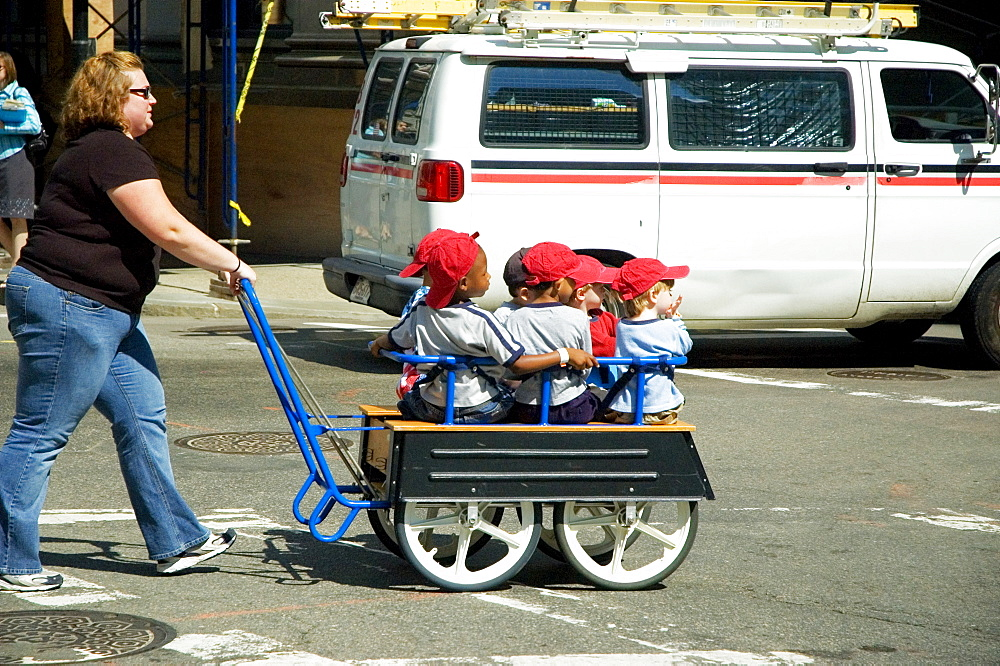 Mid adult woman pushing children in a trolley