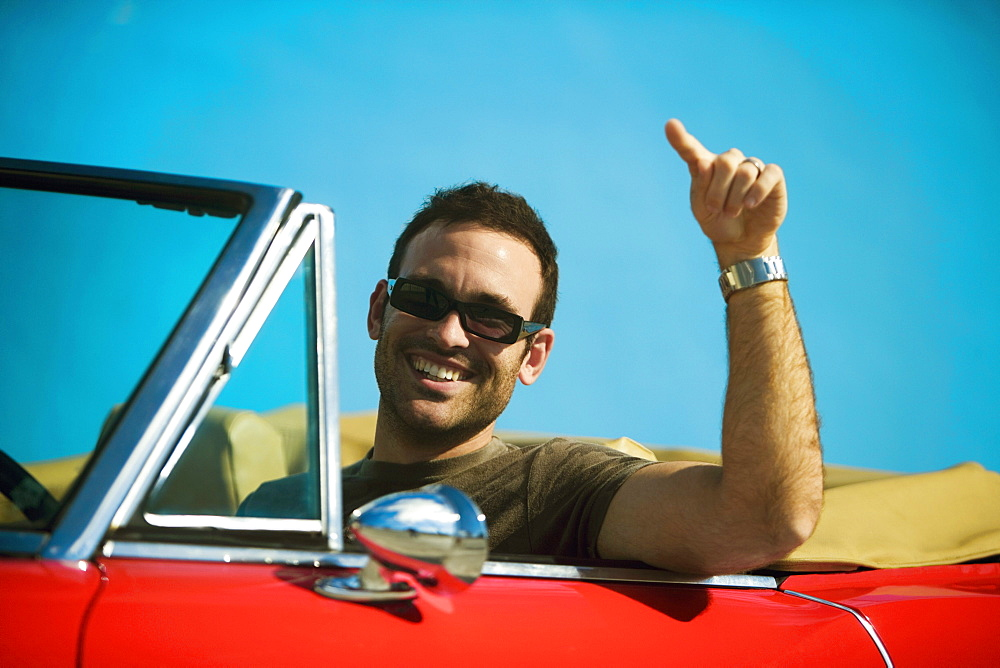 Close-up of a mid adult man sitting in a convertible car pointing forward, Miami, Florida, USA