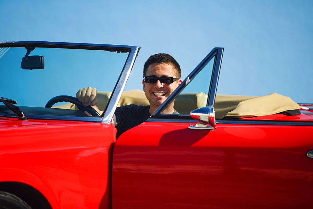 Mid adult man sitting in a convertible car, Miami, Florida, USA