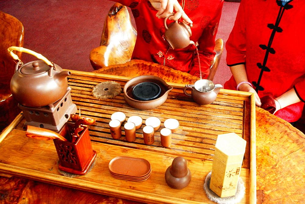 Mid section view of a woman pouring tea into a tea kettle, Tongli, Jiangsu Province, China