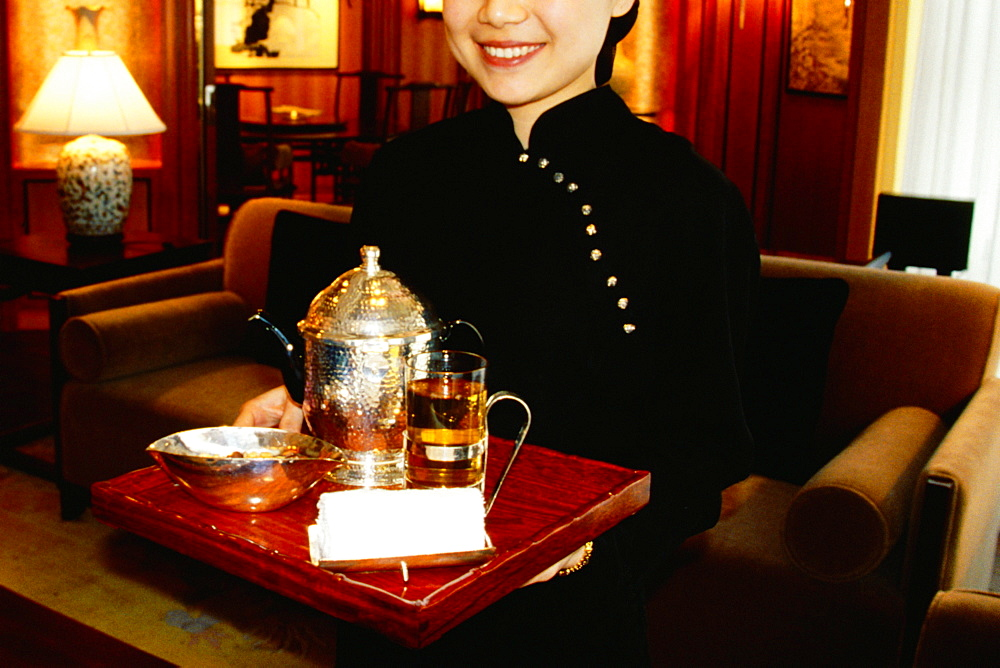 Waitress holding a serving tray and smiling, Shanghai, China