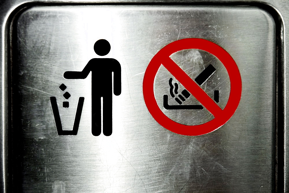 Close-up of Trash and No Smoking sign on a metal door