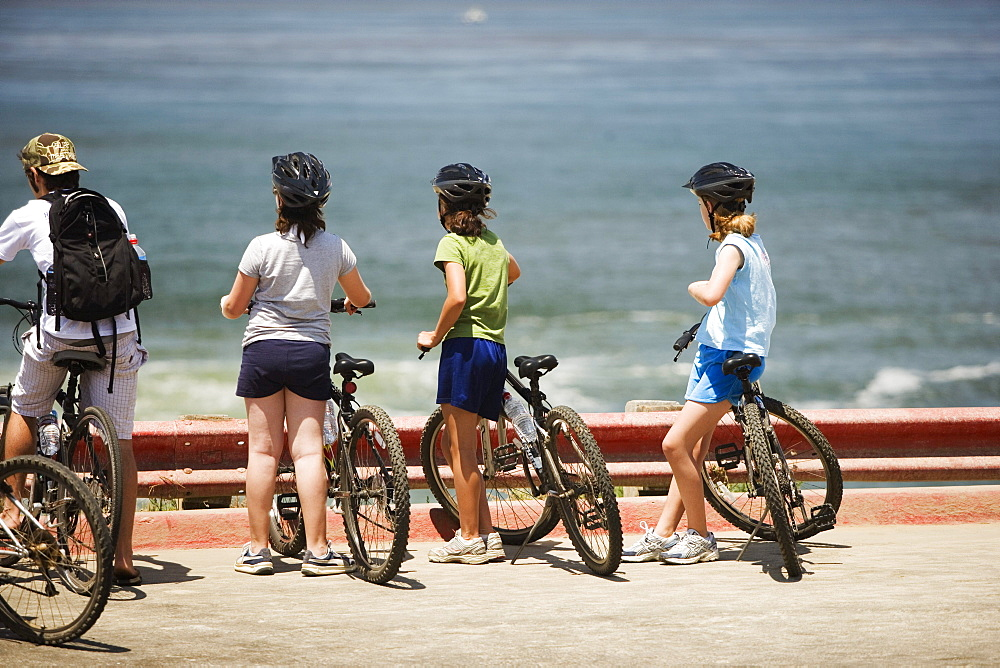 Rear view of a group of cyclists looking at the sea, La Jolla, San Diego, California, USA