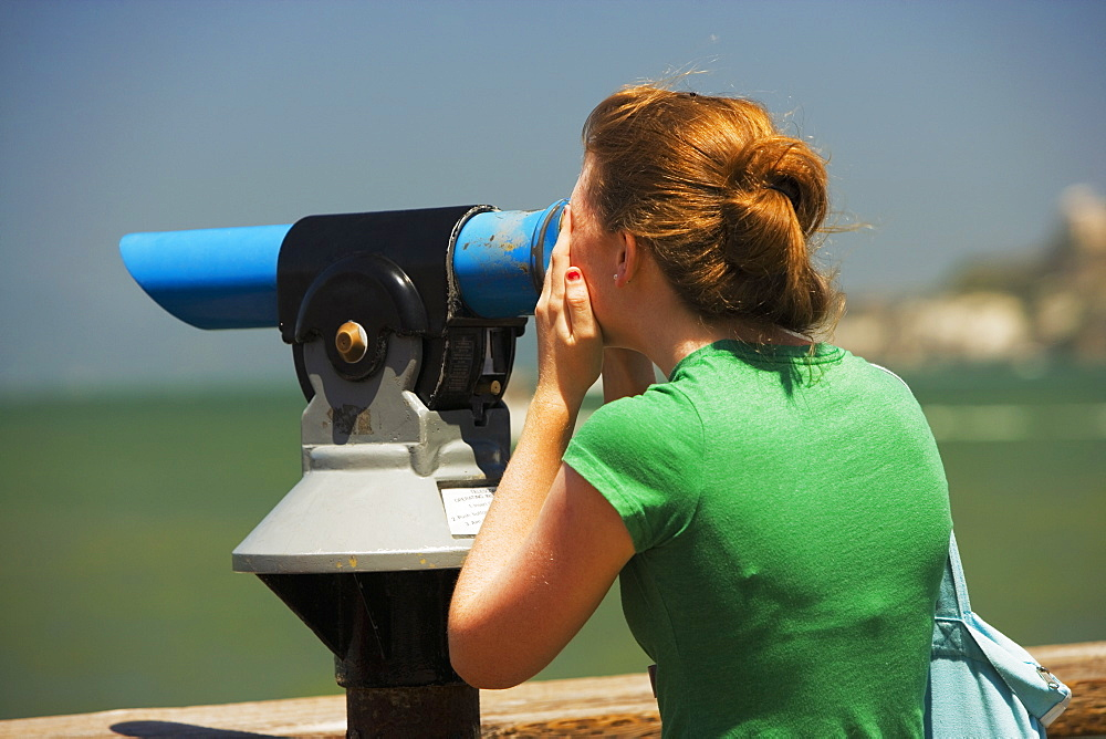 Close-up of woman looking through a hand-held telescope