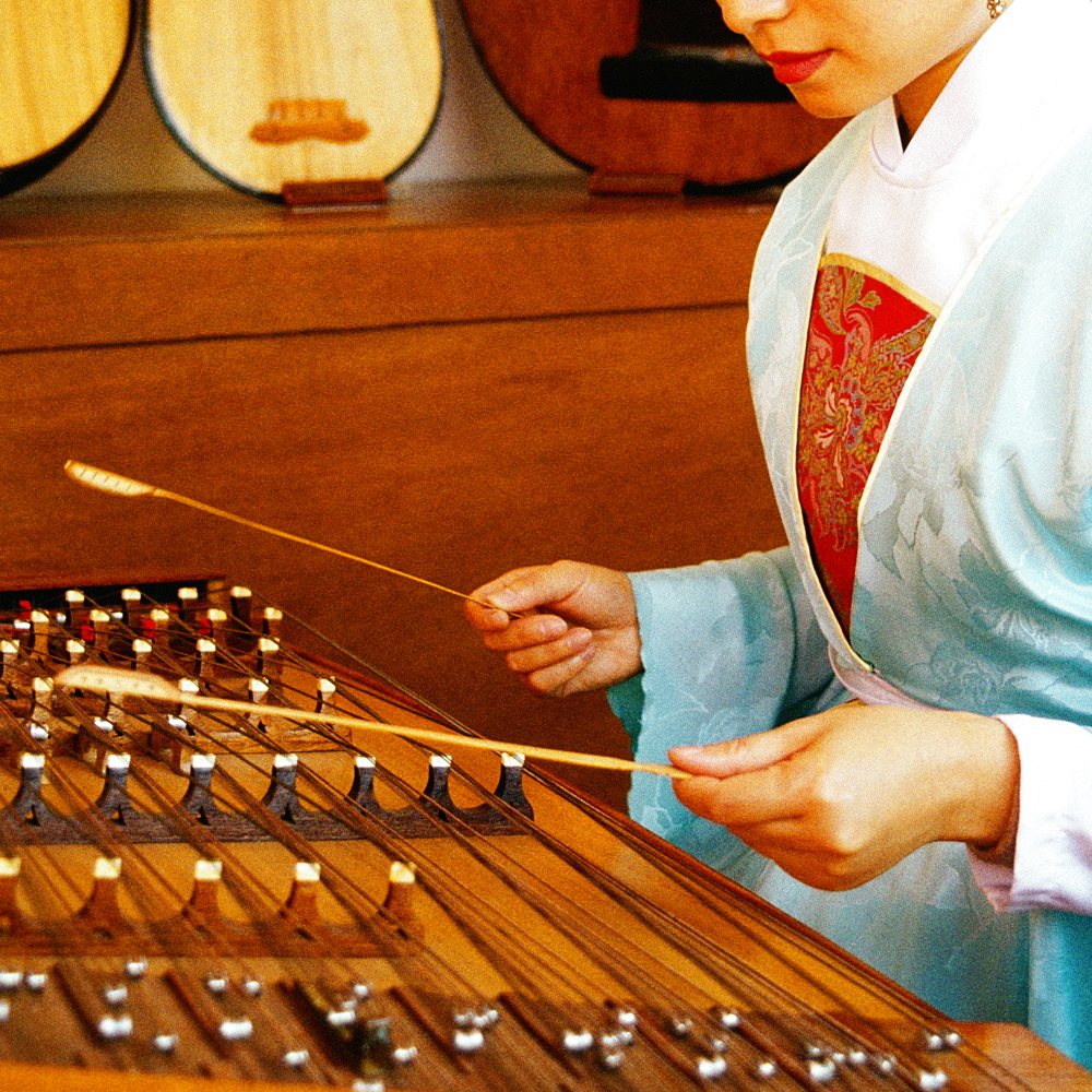 Side profile of a young woman playing dulcimer, Hong Kong, China