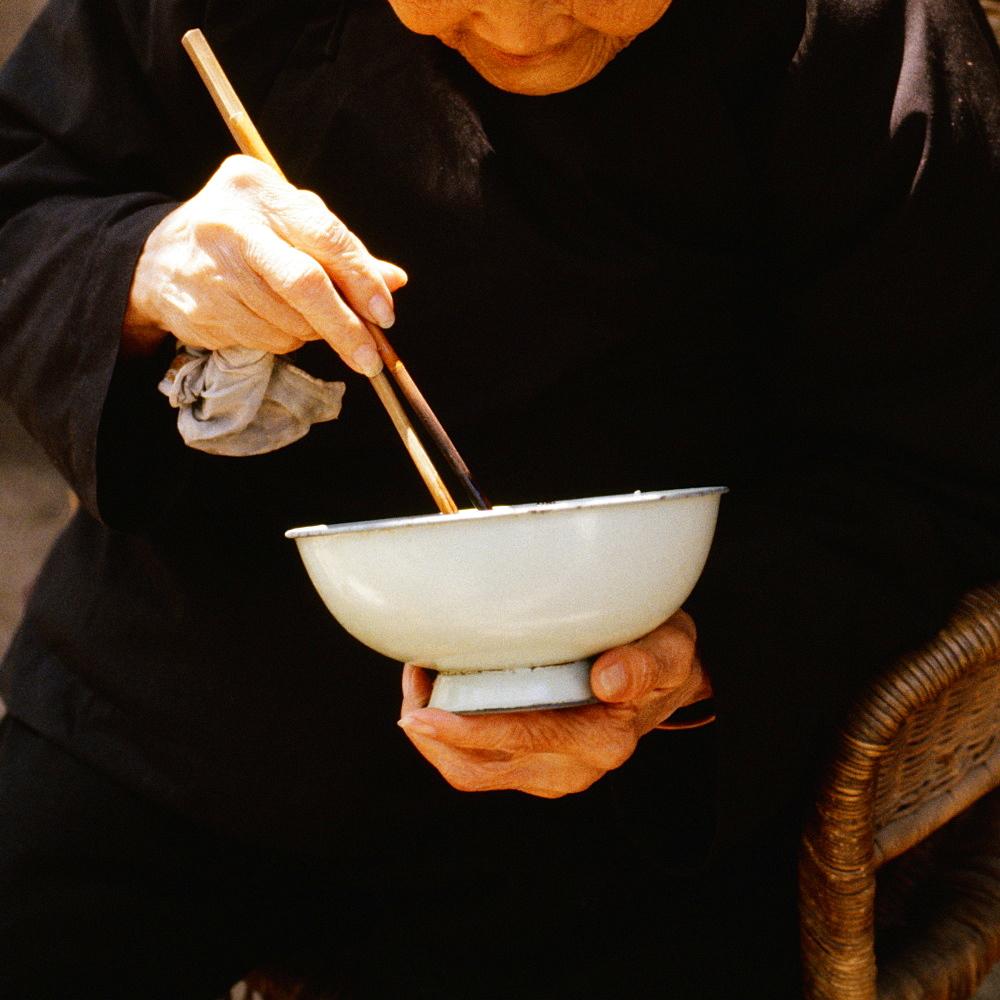 Close-up of a senior man eating with chopsticks, Xian, China