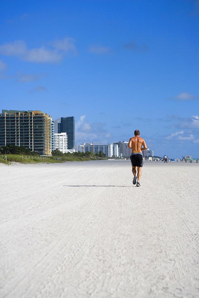 Rear view of a man jogging on the beach, South Beach, Miami Beach, Florida, USA