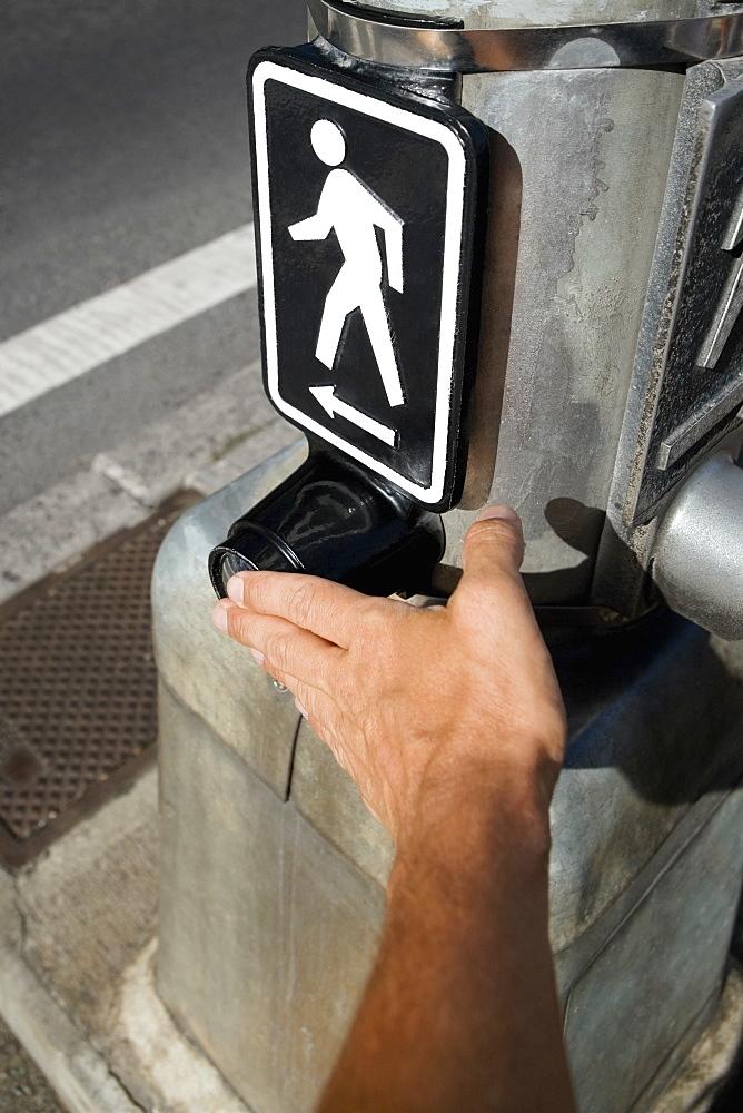 Close-up of a man's hand adjusting a pedestrian crossing signboard, Honolulu, Oahu, Hawaii Islands, USA