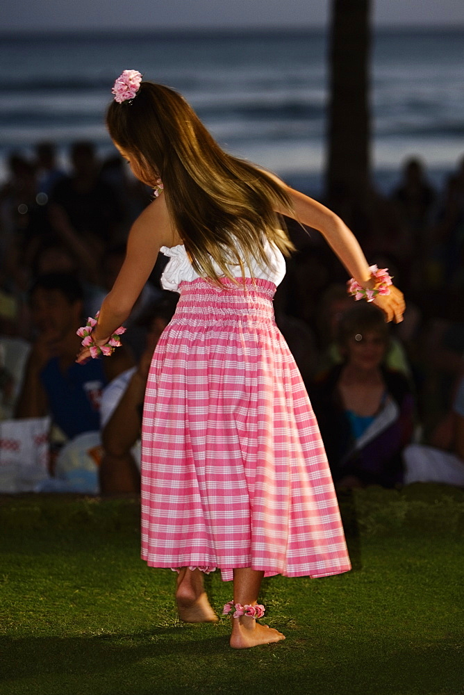 Rear view of a teenage girl hula dancing in a lawn