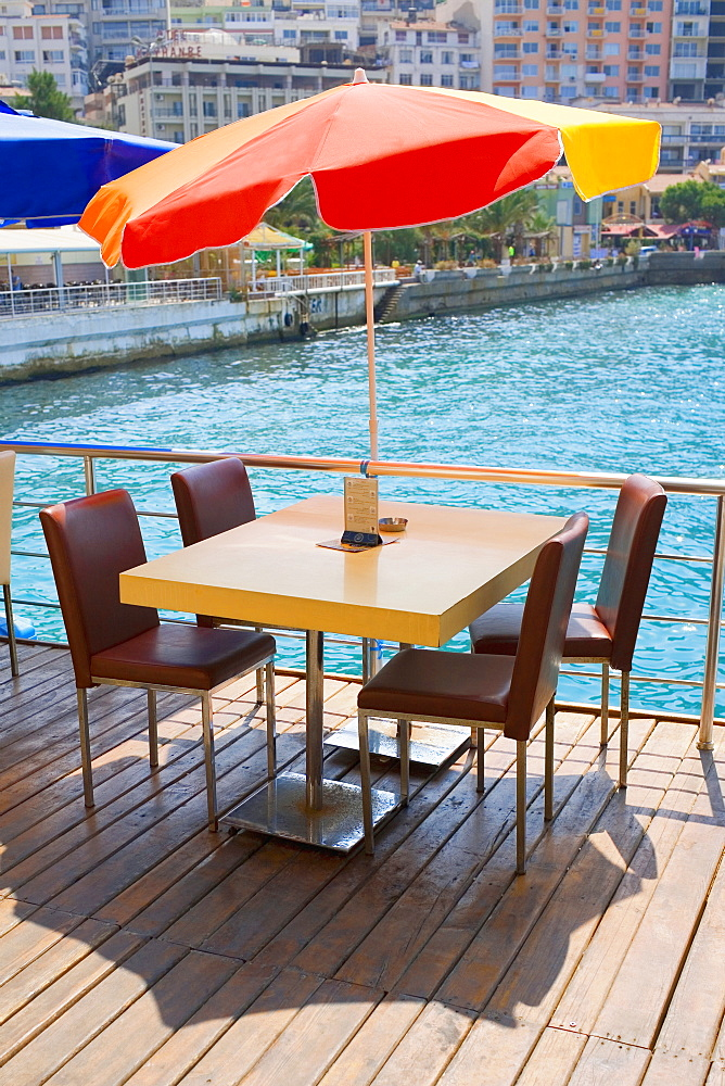 Table with four chairs under a patio umbrella in a restaurant, Ephesus, Turkey