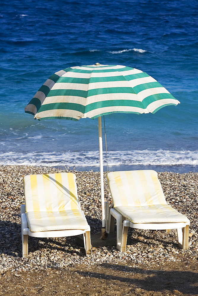 Two lounge chairs under a beach umbrella on the beach, Greece