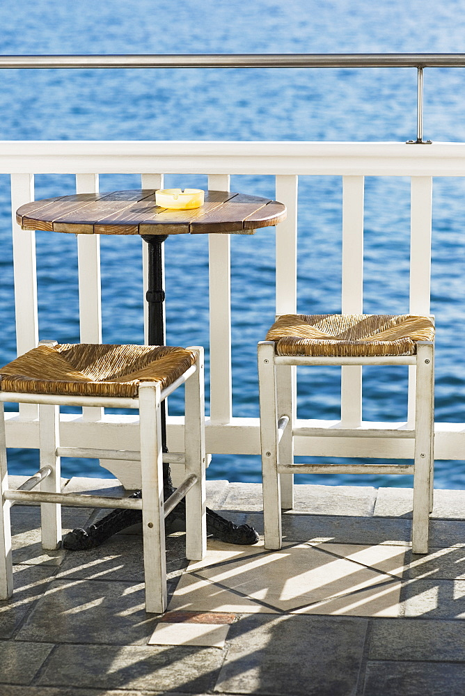 Empty table with stools near a railing in a restaurant, Mykonos, Cyclades Islands, Greece