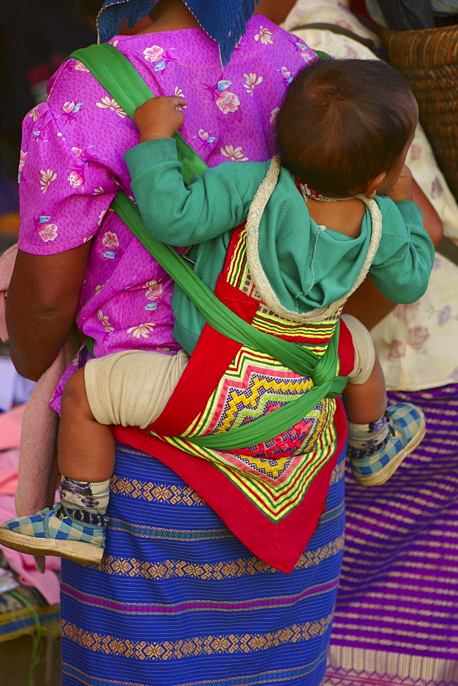 Rear view of a woman carrying her baby on her back, Luang Prabang, Laos