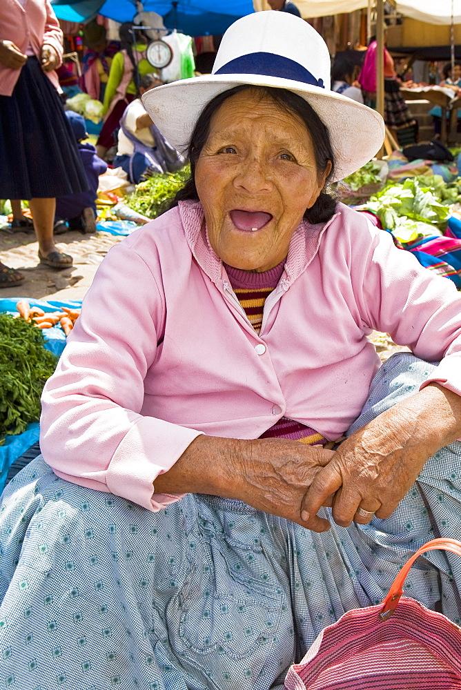 Portrait of a senior woman crouching at a market stall, Peru