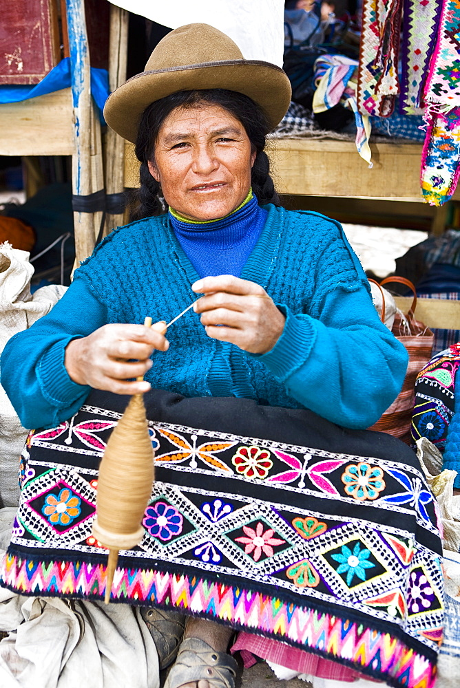 Portrait of a mature woman spinning a spool, Peru