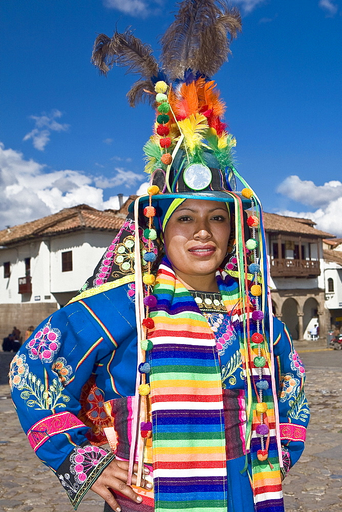 Portrait of a young woman wearing a traditional clothing and standing with arms akimbo, Peru