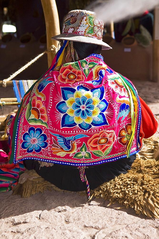 Rear view of a woman weaving in a loom, Aguanacancha, Peru