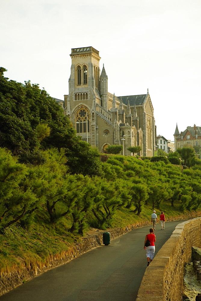 Three people walking on the road, Eglise Sainte Eugenie, Biarritz, France