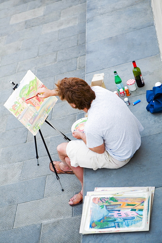 High angle view of a man painting on an easel, Italian Riviera, Genoa, Liguria, Italy
