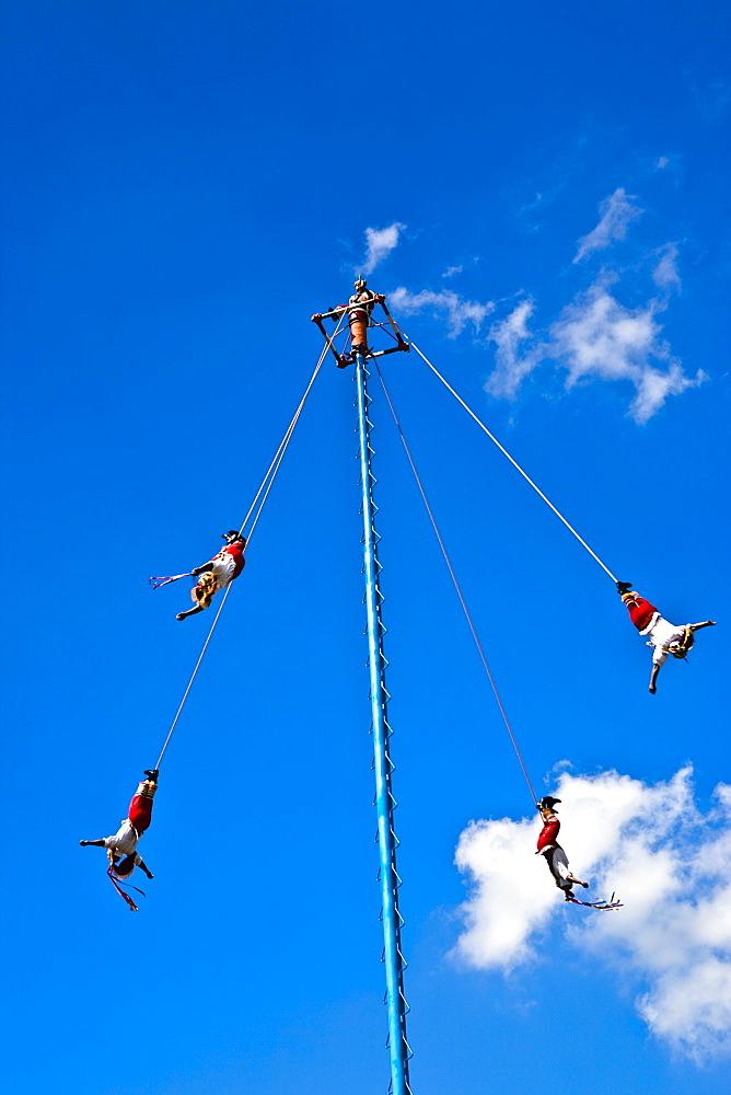 Low angle view of totonac voladores flying dancers flying from the pole, El Tajin, Veracruz, Mexico
