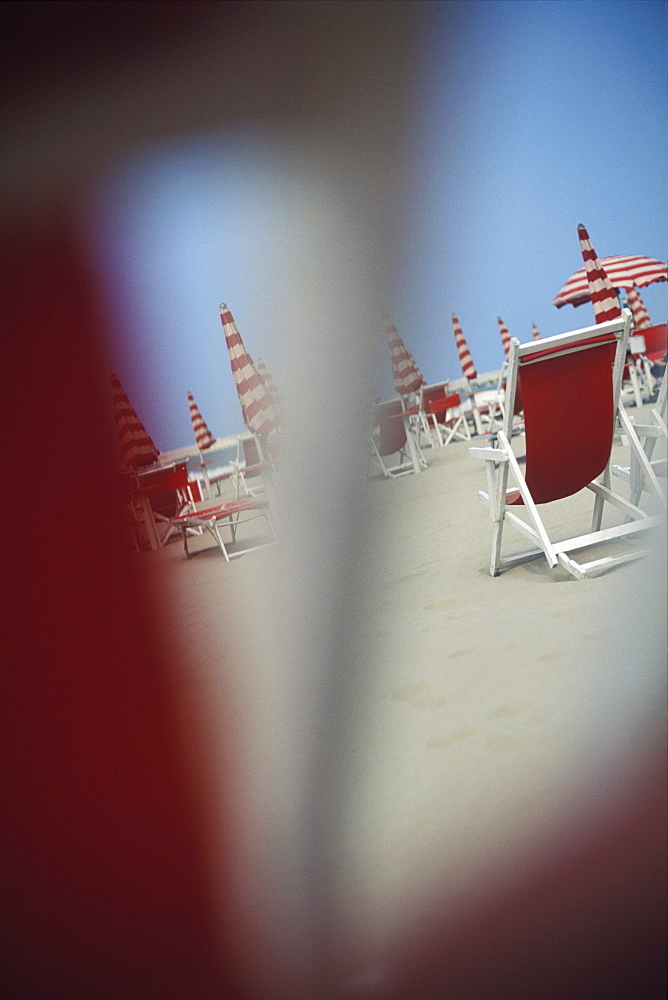 Folding chairs and beach umbrellas on the beach, Italy