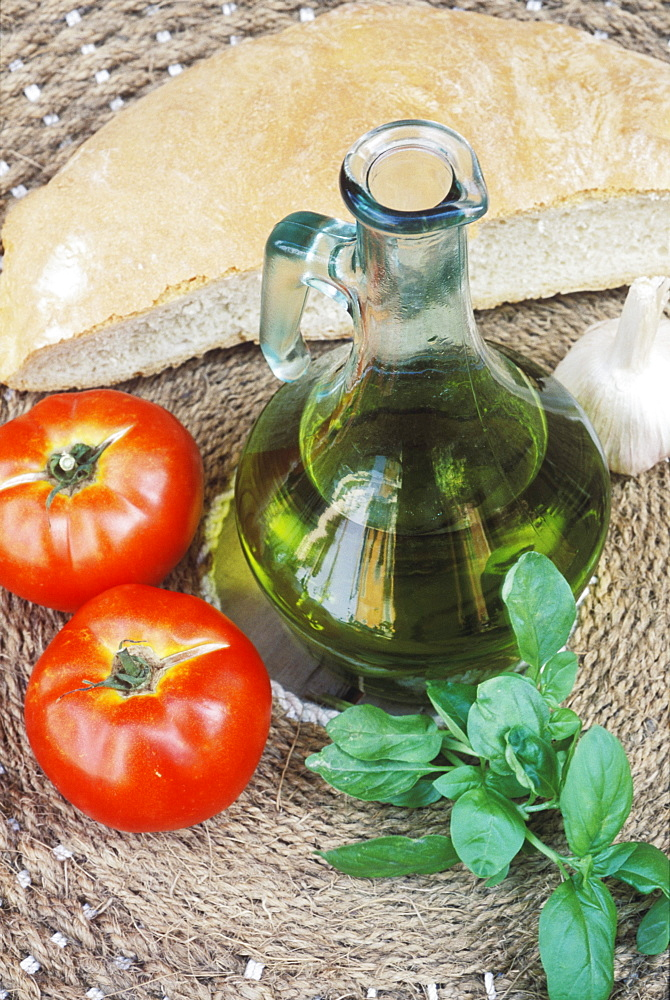 Close-up of a bottle of olive oil and two tomatoes
