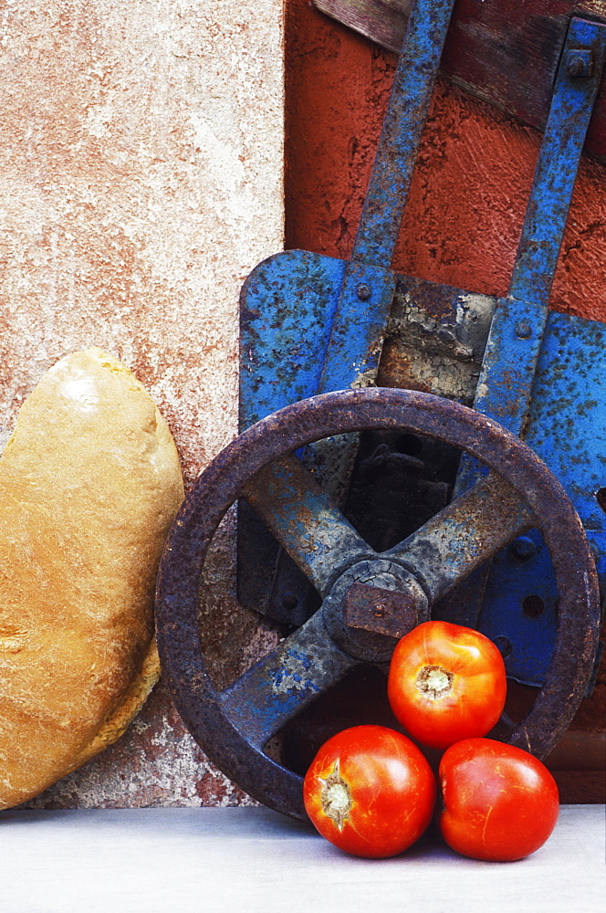 Close-up of three tomatoes near a wheel and a piece of bread