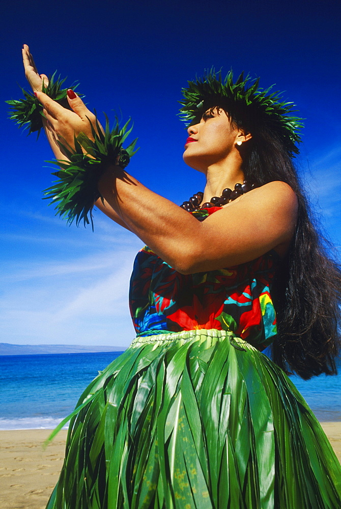 Low angle view of a hula dancer dancing on the beach, Hawaii, USA