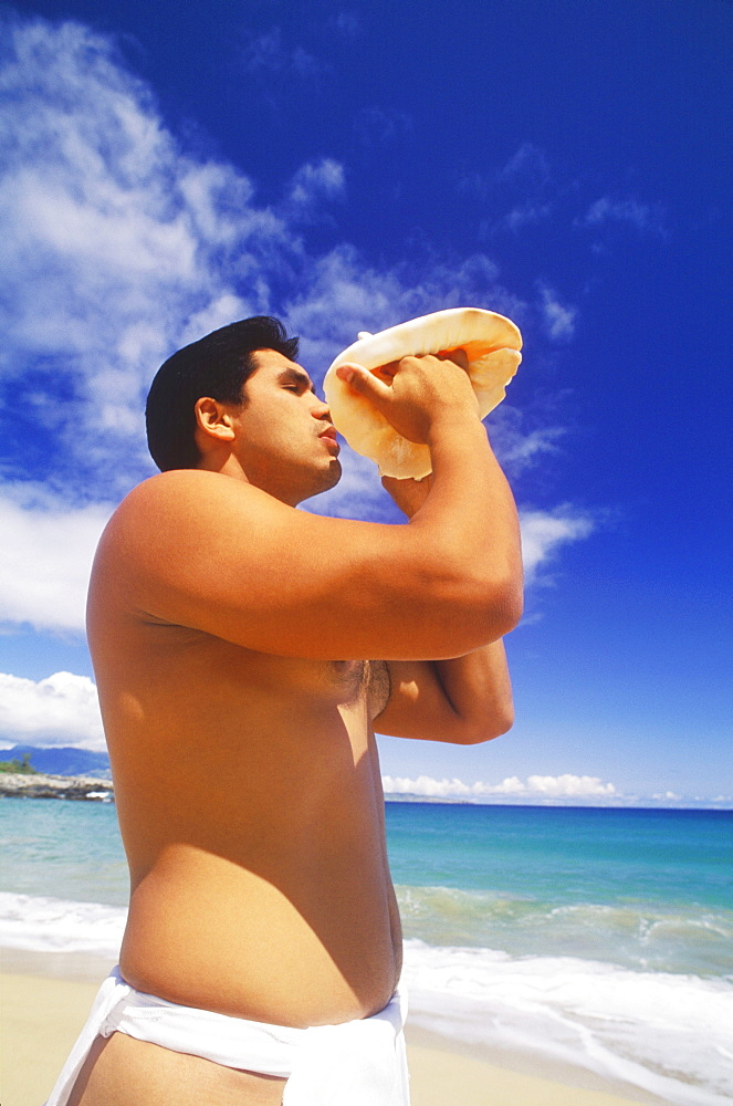 Side profile of a young man blowing a conch shell on the beach, Hawaii, USA